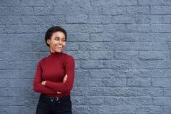 微笑对灰色墙壁的美丽的年轻黑人妇女 库存照片