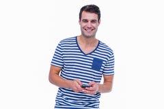 微笑对照相机和使用智能手机的英俊的行家 免版税库存图片