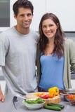 微笑对照相机和准备菜的快乐的夫妇 免版税库存照片