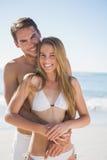微笑对照相机和拥抱的愉快的夫妇 免版税库存照片