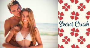 微笑对照相机和拥抱的运动夫妇的综合图象 免版税库存照片