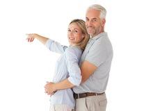 微笑对照相机和指向的愉快的夫妇 免版税库存图片