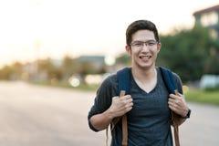微笑对照相机感觉激动,愉快的假期、喜悦和正面的年轻有吸引力的亚洲人或学院人藏品背包 免版税库存照片
