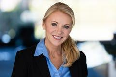 微笑对照相机的一名成熟女实业家的画象 免版税库存图片
