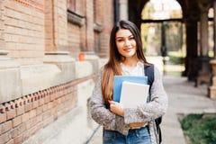 微笑对照相机的俏丽的学生外面在校园里在大学 免版税库存图片