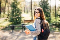 微笑对照相机的俏丽的学生外面在校园里在大学 免版税图库摄影