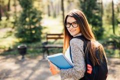微笑对照相机的俏丽的学生外面在校园里在大学 库存图片
