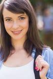 微笑对照相机的俏丽的学生外面在校园里 免版税库存图片