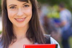 微笑对照相机的俏丽的学生外面在校园里 图库摄影