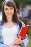 微笑对照相机的俏丽的学生外面在校园里 库存照片