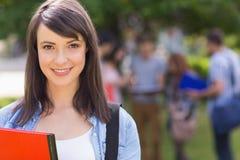 微笑对照相机的俏丽的学生外面在校园里 库存图片