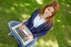 微笑对照相机的俏丽的红头发人在公园使用膝上型计算机 免版税图库摄影