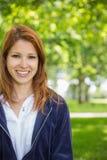 微笑对照相机的俏丽的红头发人在公园 免版税图库摄影