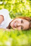 微笑对照相机的俏丽的红头发人说谎在草 图库摄影