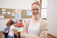 微笑对照相机的俏丽的老师在教室顶部 免版税库存照片