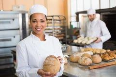 微笑对照相机的俏丽的面包师用大面包 库存图片