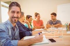 微笑对照相机的偶然商人在会议期间 库存图片