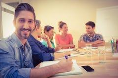 微笑对照相机的偶然商人在会议期间 免版税库存照片