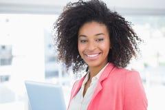 微笑对照相机的偶然女实业家拿着片剂个人计算机 免版税库存图片