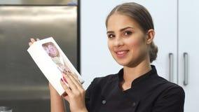 微笑对照相机的可爱的女性面包师拿着蛋白软糖弓  股票录像