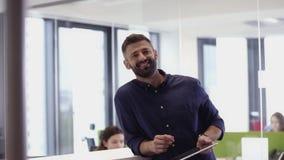 微笑对照相机的商人,使用片剂在办公室