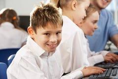 微笑对照相机的学校课程的男孩 免版税库存图片