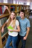 微笑对照相机的学生在图书馆里 库存图片