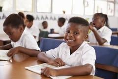 微笑对照相机的小学男孩对他的在类的书桌 图库摄影