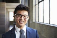 微笑对照相机的年轻亚洲商人 库存照片