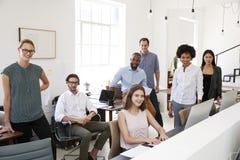 微笑对照相机的年轻企业同事在他们的办公室 免版税库存照片