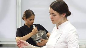 微笑对照相机的年轻可爱的女性厨师,当烹调时 影视素材