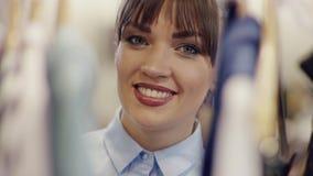 微笑对照相机的年轻女人接近的射击从在一个机架的衣裳的后面在clothiong商店 股票视频