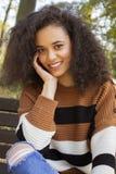 微笑对照相机的年轻快乐的妇女 免版税库存图片
