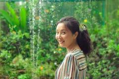 微笑对照相机的愉快的女孩在庭院里 库存图片