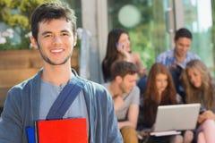 微笑对照相机的愉快的学生外面在校园里 库存图片