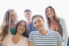 微笑对照相机的愉快的学生外面在校园里 免版税库存图片