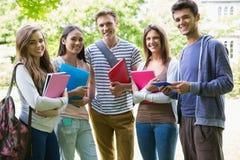 微笑对照相机的愉快的学生外面在校园里 图库摄影
