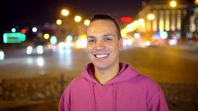 微笑对照相机的愉快的年轻人在城市 看照相机的一个人的画象 年轻种族人微笑 股票视频