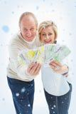 微笑对照相机的愉快的成熟夫妇的综合图象显示金钱 免版税库存照片