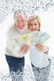 微笑对照相机的愉快的成熟夫妇的综合图象显示金钱 库存照片