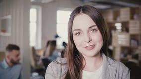 微笑对照相机的愉快的美丽的白种人年轻经理 摆在现代办公室4K的正面母上司画象  影视素材