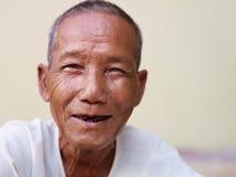 微笑对照相机的愉快的老亚裔人纵向  免版税图库摄影