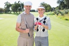 微笑对照相机的打高尔夫球的夫妇拿着俱乐部 库存照片