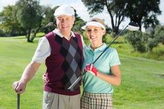微笑对照相机的打高尔夫球的夫妇 库存照片