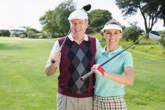 微笑对照相机的打高尔夫球的夫妇 免版税库存图片