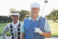 微笑对照相机的打高尔夫球的夫妇 免版税库存照片