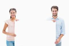 微笑对照相机的有吸引力的年轻夫妇拿着海报 免版税库存照片