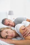 微笑对照相机的白肤金发的妇女作为丈夫睡觉 免版税库存图片