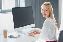 微笑对照相机的美丽的年轻女实业家,当与台式计算机一起使用时 库存图片
