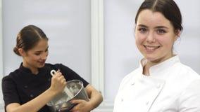 微笑对照相机的美丽的年轻女性厨师对kithchen 影视素材